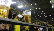 Zwei halbvolle Becher Bier stehen auf einem Geländer im Signal-Iduna-Park von Dortmund