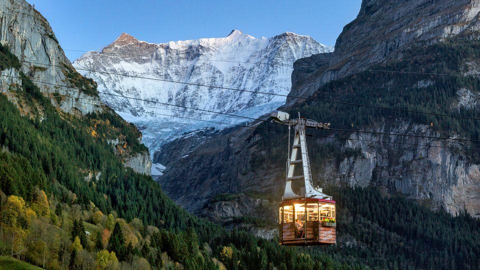 Bild 1 von 11 der Fotostrecke zum Klicken:Luftseilbahn Grindelwald, Schweiz  Tagsüber drängen sich Wanderer mit Rucksäcken oder Rodler in warmer Winterkleidung in den Gondeln der Pfingsteggbahn – am Abend verwandeln sich diese dann in gemütliche kleine Gourmetlokale und laden zum Sky-Dinner. Leise schweben sie in den letzten Sonnenstrahlen den majestätischen Felswänden entgegen oder baumeln unter einem sagenhaft klaren Sternenhimmel.