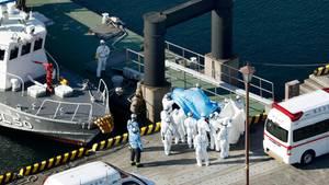 Medizinisches Personal in Schutzanzügen begleitet im Hafen von Yokohama einen Passagier