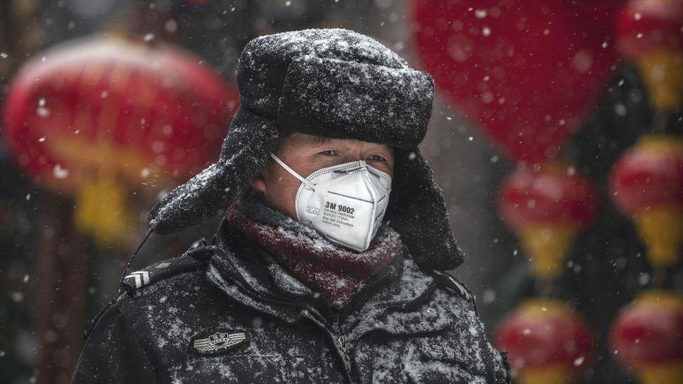 Peking, China: Ein Wachmann trägt eine Atemmaske.