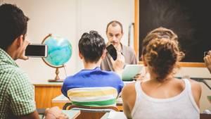 Ein Lehrer wird von zwei Schülern im Klassenraum per Handy gefilmt