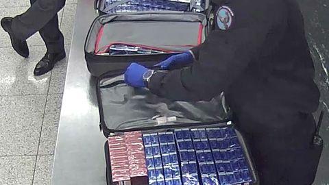 Ein Zollbeamter kontrolliert die Reisekoffer des Mannes mit den Zigaretten