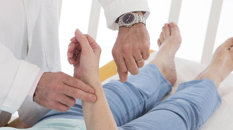 Puls messen: Ein Arzt misst per Hand und Armbanduhr den Puls einer Patientin
