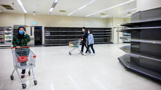 Hongkong: Käufer mit Schutzmasken gehenan leeren Supermarktregalen vorbei,
