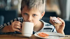 Ein Junge trinkt aus einer Tasse und hält ein Schinkenbrot in der Hand