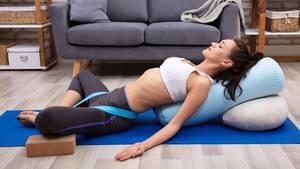 Beim Yoga unterstützt ein Kissen die Übungen