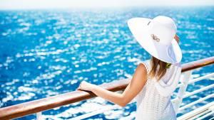 Eine Frau steht an der Reling eines Kreuzfahrtschiffes