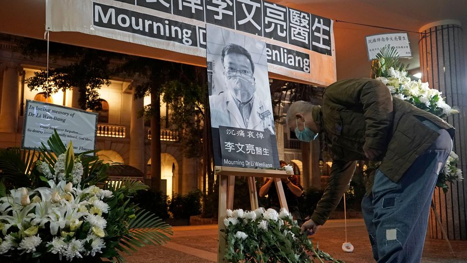 EinMann mit einem Mundschutz legt in Hongkong Blumen vor einem Bild Li Wenliangs nieder