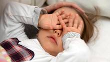 zweijähriges Mädchen reibt sich vor Müdigkeit die Augen