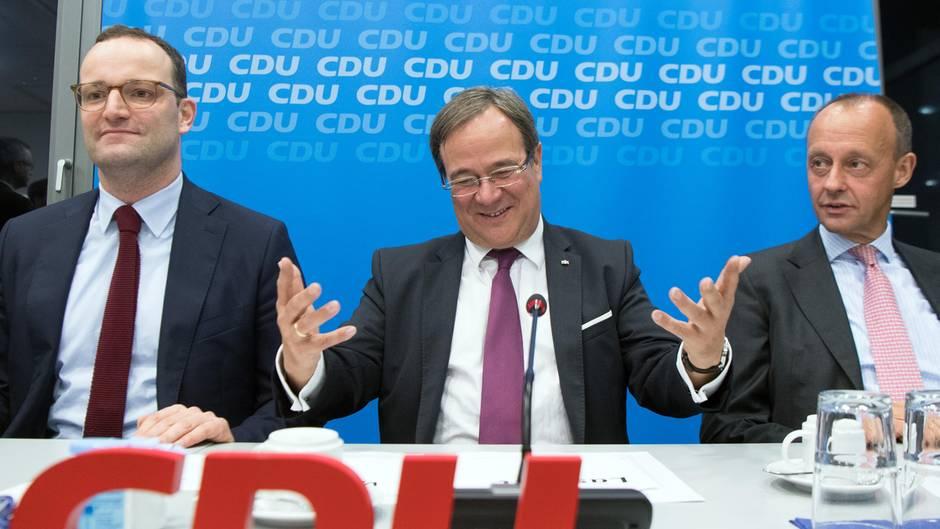 Vor einer blauen Wand mit helleren CDU-Logos sitzen drei Männer mit Anzügen und Krawatten an einem Tisch mit Mikrofonen