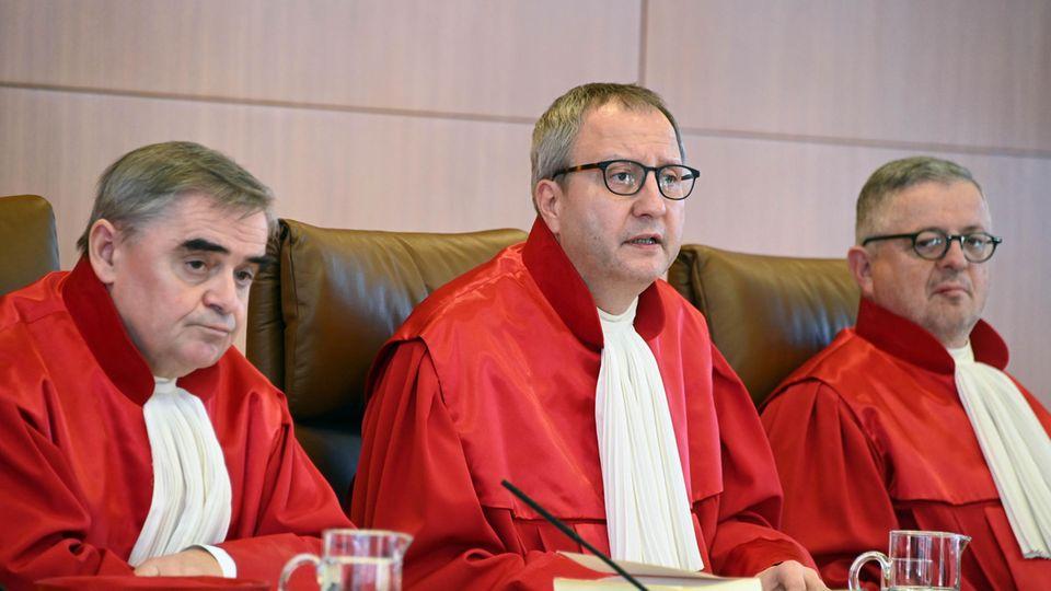 Drei Männer in roten Roben sitzen nebeneinander auf der Richterbank