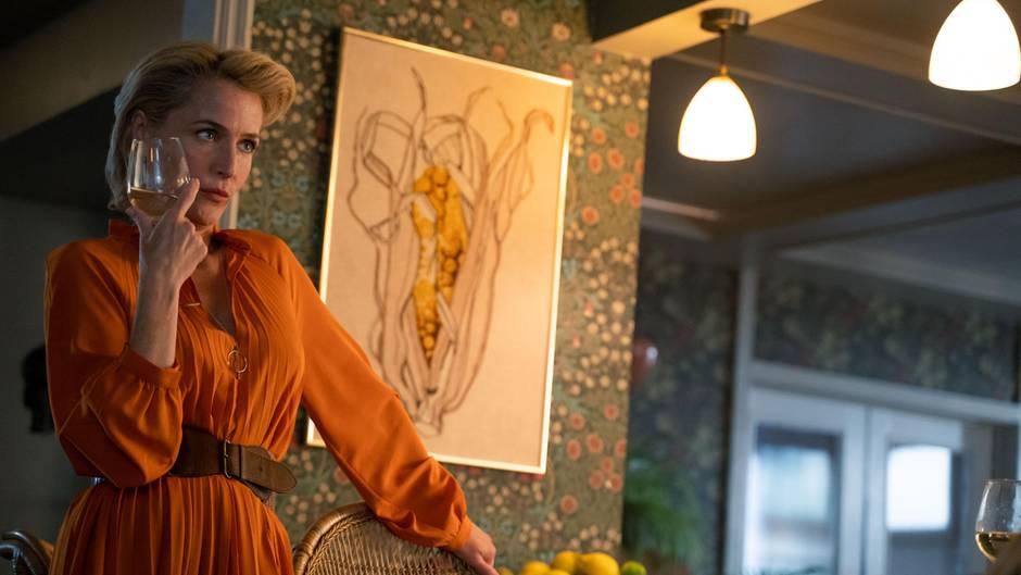Protagonistin Jean mit einem Glas Wein in der Hand. Hinter ihr ein Bild mit einem Maiskolben, der wie eine Vulva aussieht.