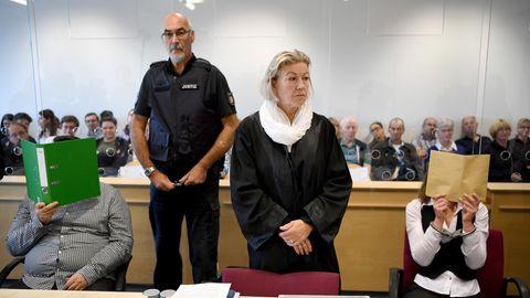 Ein Foto vom Prozessauftakt im vergangenen August: Die beiden Angeklagten verdecken ihre Gesichter