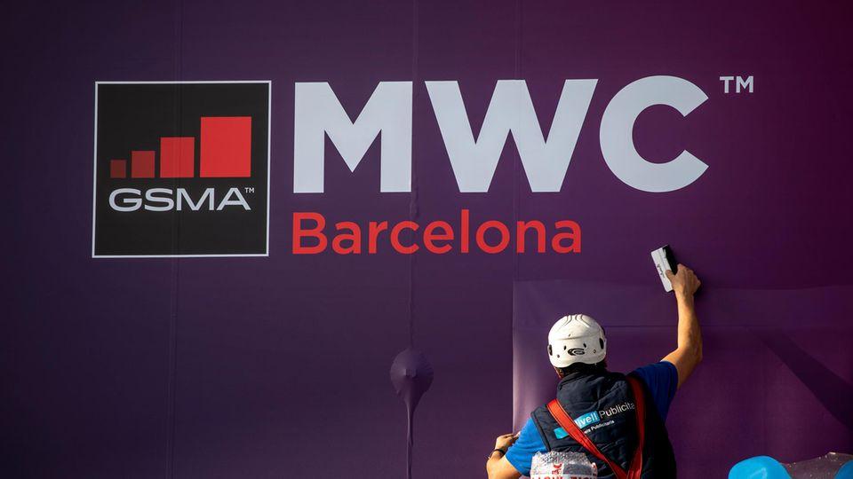 Arbeiter putzt Fenster am Ausgang des WMC-Geländes in Barcelona