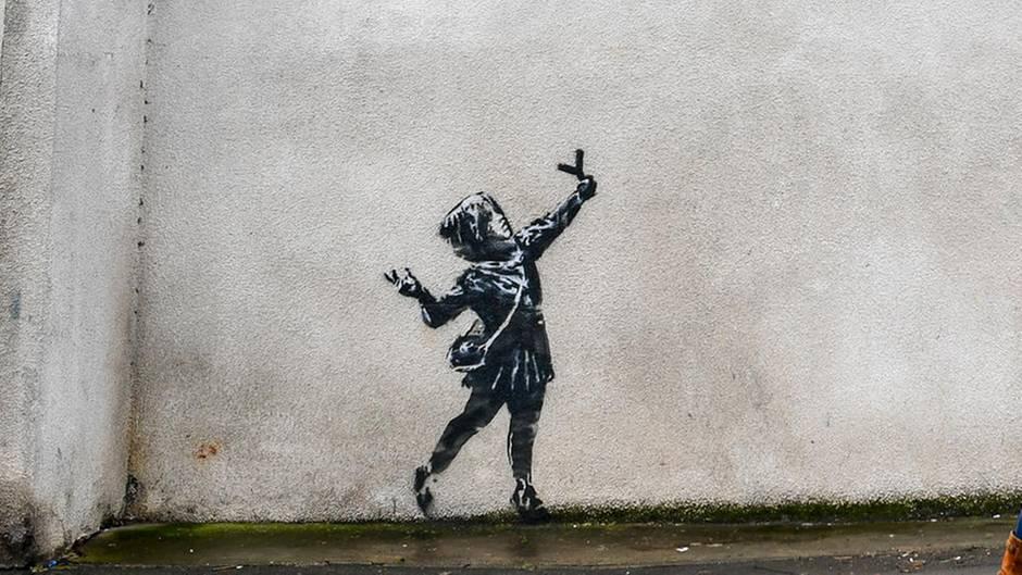 Eine Frau geht an einer Hauswand an einem Streetart-Werk vorbei, das ein Mädchen mit einer Steinschleuder in der Hand darstellt. Über dem Mädchen istein riesiger roter Klecks aus roten Blumen zu sehen.
