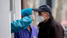 Ein älterer Mann mit Mundschutz wartet, bis ein Offizieller in Schutzkleidung ihm an der Stirn Fieber gemessen hat