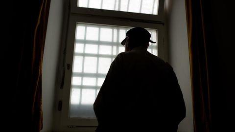 Mann vor vergittertem Gefängnisfenster