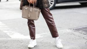 Frau trägt Turnschuhe und Handtasche