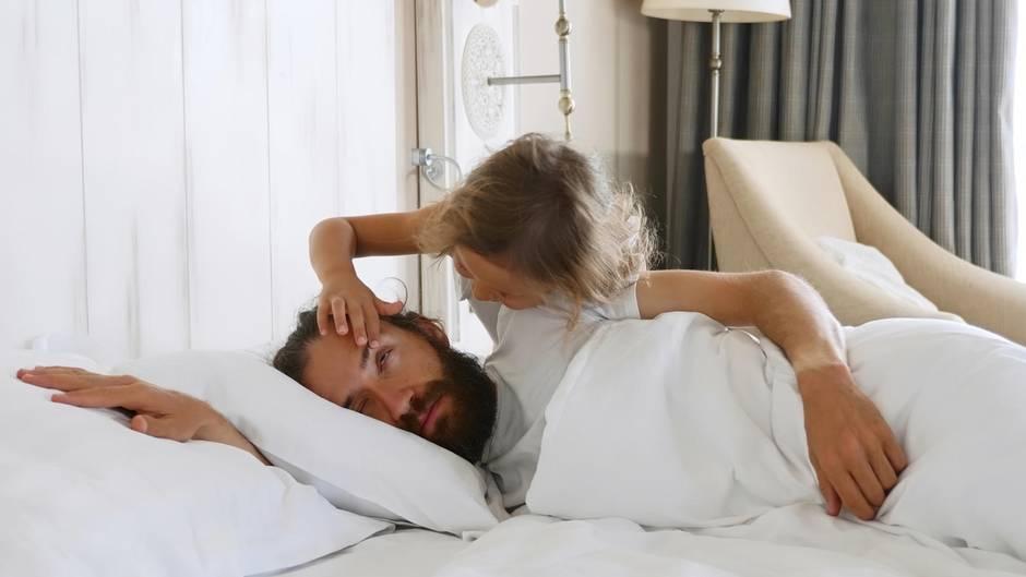 Ein Kind zieht seinem Vater am Augenlid