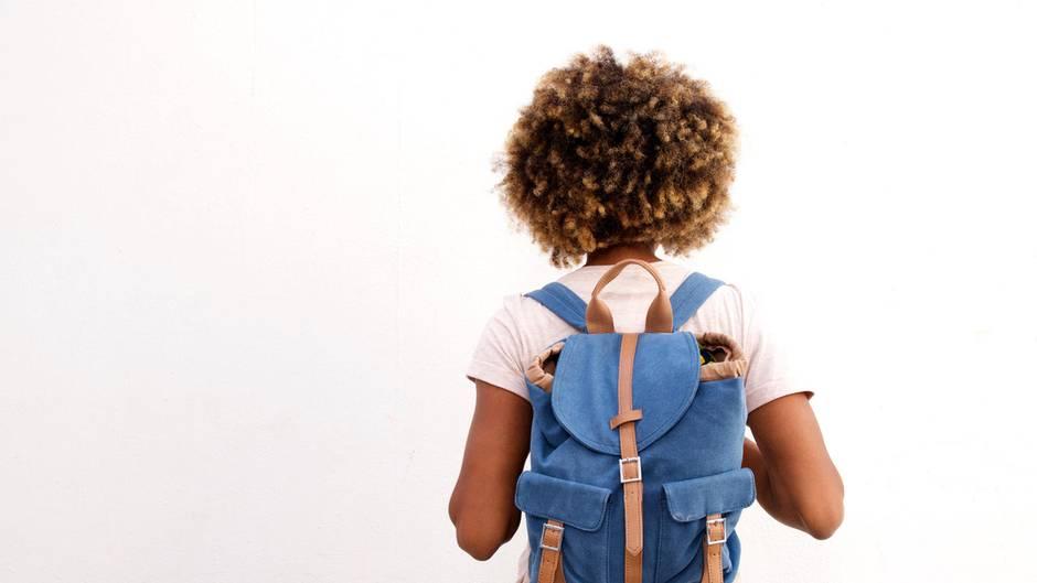 Eine junge Frau mit Afro und Rucksack
