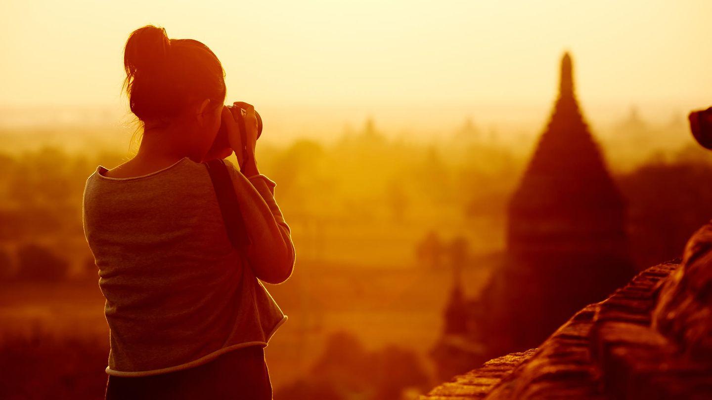Eine Frau fotografiert eine Tempelanlage in Myanmar