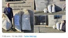 Ein Abgeordneter steht mit drei Säcken voller Kassenbons vor dem Bundesfinanzministerium