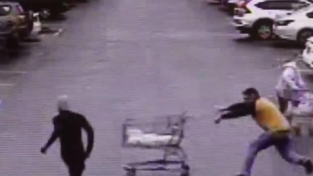 Zwei Personen, Mann stößt Einkaufswagen