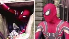 Ein Mann im Spiderman-Kostüm sammelt Müll