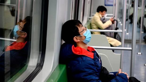 Leere U-Bahn in Shanghai mit zwei Atemmasken tragenden Fahrgästen