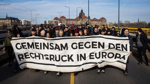 """Hinter einem Plakat mit der Aufschrift """"Gemeinsam gegen den Rechtsruck in Europa"""" stehen Demonstranten"""