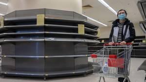 Eine Frau mit Mundschutz schiebt einen Einkaufswagen an leeren Supermarktregalen vorbei