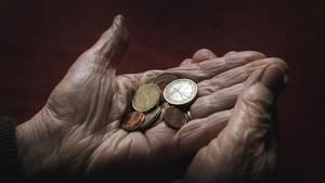 Eine 83-jährige Frau hält verschiedene Euromünzen