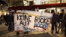 Gegendemonstranten zeigen mit Plakaten ihre Haltung zu Björn Höcke