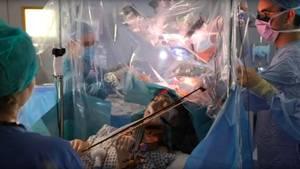 Eine Patientin spielt Geige, während Chirurgen einen Tumor aus ihrem Gehirn entfernen.