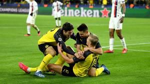 Drei Dortmunder Spieler jubeln auf den Rasen, während PSG-Spieler konsterniert im Hintergrund stehen