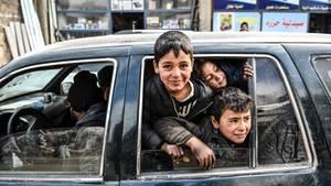 Kinder schauen aus dem Fenster eines Autos