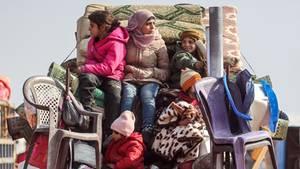 Kindersitzen auf der Ladefläche eines Kleintransporters auf den Habseligkeiten ihrer Familie