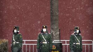 Chinesische Polizisten stehen bei Schneefall in der in der Nähe des Platzes des Himmlischen Friedens und tragen einen Mundschutz