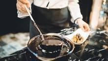 Ein Koch schöpft Schokoladensauce aus einem Topf