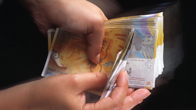 Eine Person hält ein Bündel Zehnernoten in Schweizer Franken in den Händen
