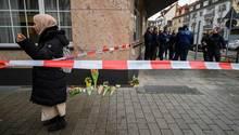 Blumen und Kerzen liegen in der Nähe eines Tatorts in Hanau