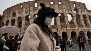 Eine Touristin aus China trägt während eines Besuchs des Kolosseums einen Mundschutz