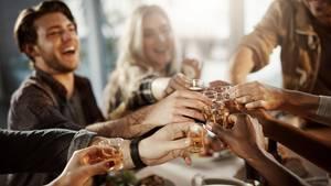 Schnaps Verdauung: Freunde stoßen in einem Restaurant mit kleinen Schnapsgläsern an