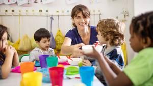 Erzieherin mit Kindern beim Essen