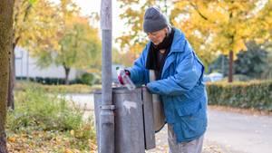 Eine Frau sucht in einem Mülleimer nach Pfandflaschen
