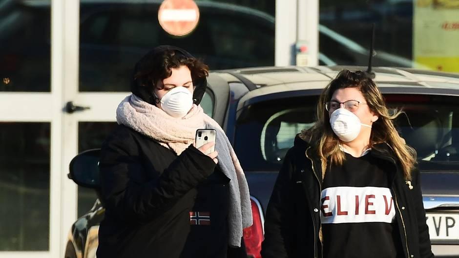 In der Stadt Codogno südwestlich von Mailand kehren zwei Frauen mit Schutzmaskenvor dem geschlossen Supermarkt um