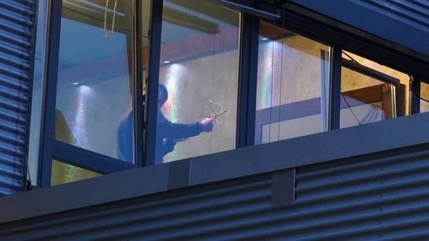 Ein Ermittler untersucht ein Einschussloch in einer Fensterscheibe der Shisha-Bar in Stuttgart