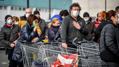 Menschen tragen Atemschutzmasken und stehen vor einem Supermarkt in einer Schlange
