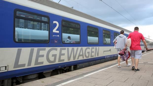 Reisende gehen zu einem Nachtzug (EuroNight) der ÖBB (Österreichische Bundesbahnen)
