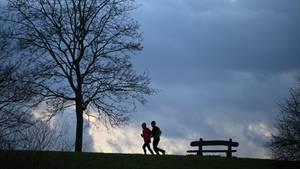 Zwei Läufer in der Kasseler Fulda-Aue vor einer dunklen Wolkenwand
